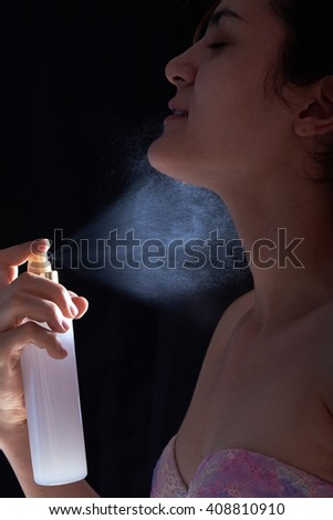 young woman apply perfume isolated on black background - stock photo