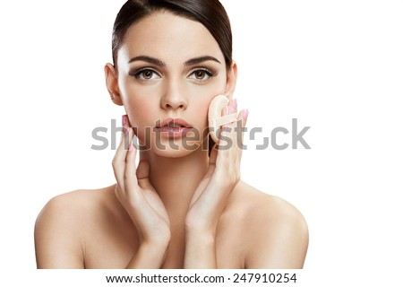 Young woman applying blusher on her face with powder puff, skin care concept / photo composition of brunette girl  - isolated on white background  - stock photo