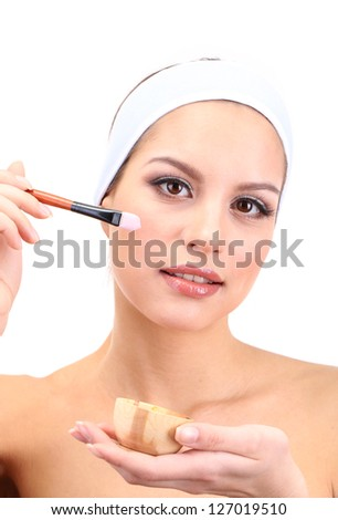 Young woman applying clay facial mask, isolated on white