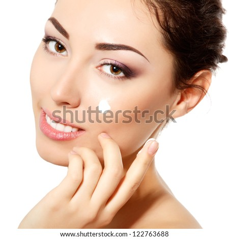 young woman applying cream on face with fresh clean skin, over white background