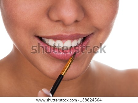 Young Woman Applying Lipstick Over White Background - stock photo