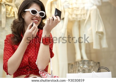 Young woman applying lipstick while sitting down with shopping bags. - stock photo
