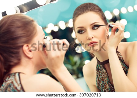 Young woman applying mascara, focus on the reflection in the mirror