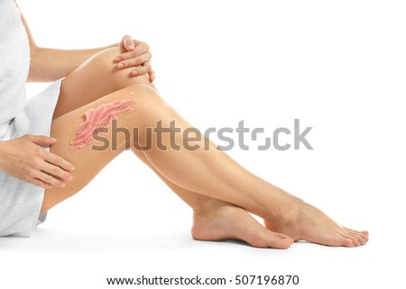 Young woman applying nourishing scrub on leg and sitting on white background