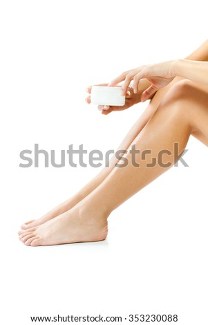 Young woman applying skin cream on her body