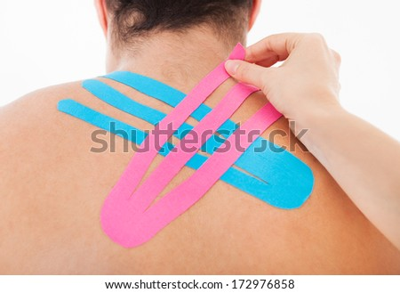 Young Woman Applying Special Physio Tape On Man's Back - stock photo