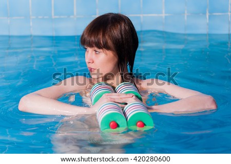 Young woman aquaaerobic training in fitness center pool - stock photo
