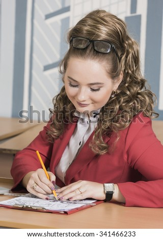 Young woman architect in red suit sitting at a table in front of the drawings. Computer is on the table. Female student with a pencil. Director.