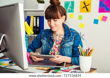 young woman artist drawing something on graphic tablet at the office