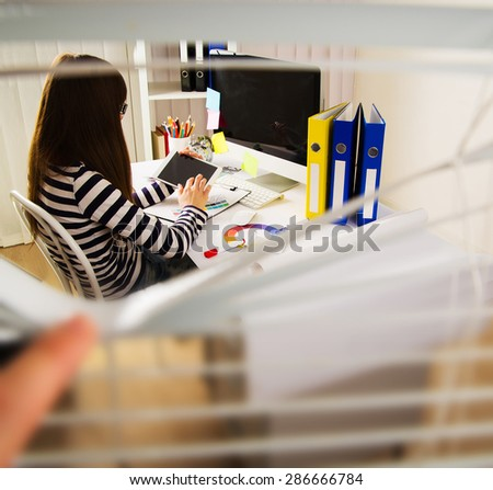 young woman artist drawing something on graphic tablet at the office. Photo through the blinds - stock photo
