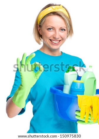 Young woman as a cleaning maid holding bucket full of liquids and showing OK sign, isolated over white - stock photo