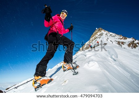 Young woman ascending steep ridge to the summit