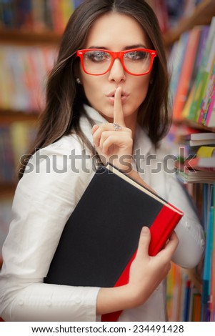 Young Woman Asking for Silence in the Library Room - Portrait of a woman doing a quiet request gesture  - stock photo