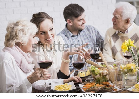 Young woman at a dinner table gossiping with her mother-in-law and drinking wine