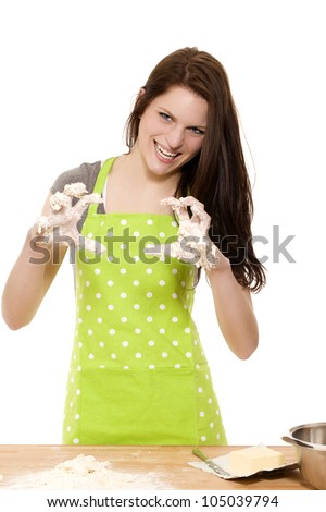 young woman at baking forming claws with her messy dough covered hands on white background - stock photo