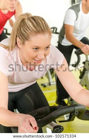 Young woman at bike class enjoy cardio training - stock photo