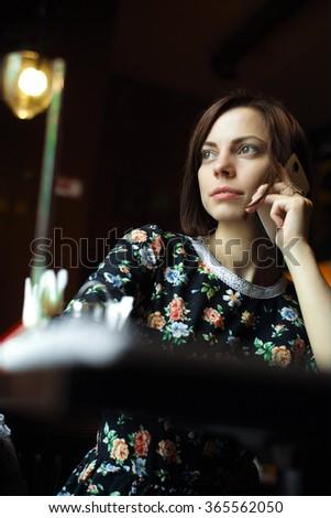 Young woman at cafe  talking on the mobile phone - stock photo