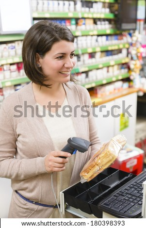 Young woman at cash register in a store using price scanner