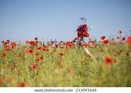 Young woman  at dress drowns in poppy field - stock photo