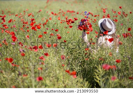 Young woman  at dress walk in poppy field - stock photo