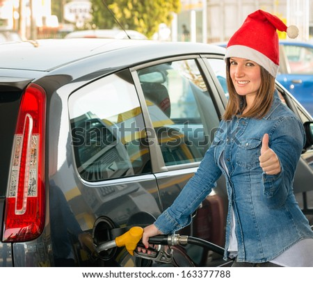 Young woman at gas station with Santa hat - stock photo