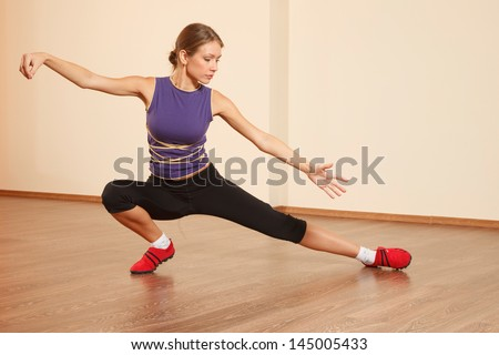 Young woman at gym is practicing Tai Chi