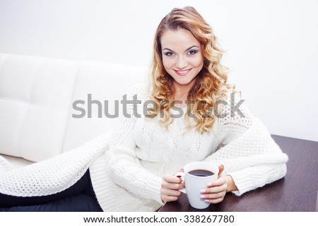 Young woman at home drinking hot coffee, wrapped in a scarf,  white background, place for your text - stock photo