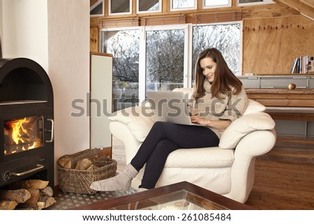 Young woman at home in chair using laptop - stock photo