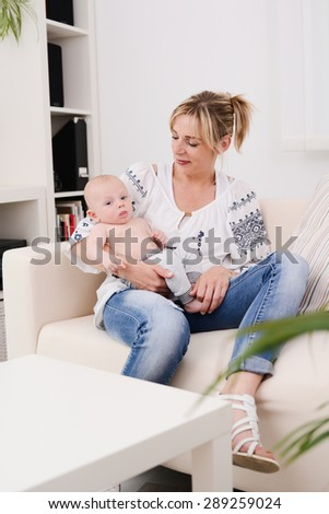 young woman at home playing and taking care of lovely new born baby boy  - stock photo