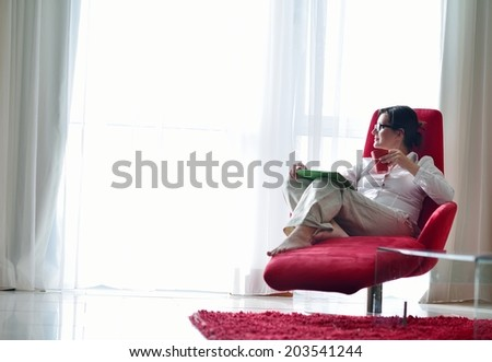 Young woman at home relaxing in her lliving room reading a digital tablet PC surf internet and work - stock photo