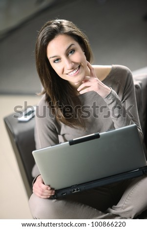 young woman at home, relaxing on a brown leather sofa with her laptop.