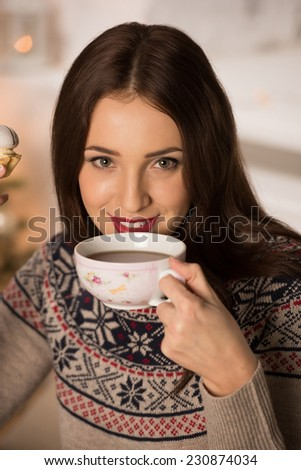 Young woman at home sipping tea from a cup - stock photo