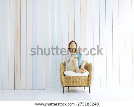 Young woman at home sitting on modern chair - stock photo