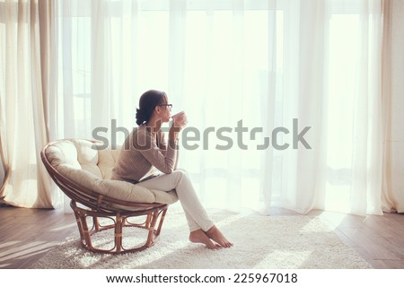 Young woman at home sitting on modern chair in front of window relaxing in her living room and drinking coffee or tea - stock photo
