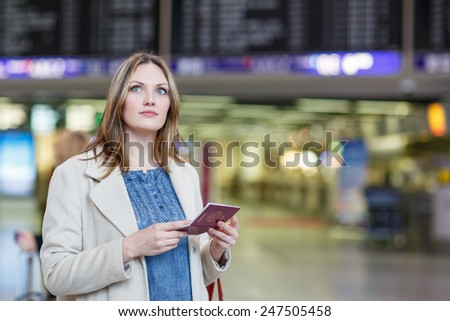 Young woman  at international airport, checking electronic board and waiting for her flight. Female passenger with european passport at departure terminal, indoors. - stock photo