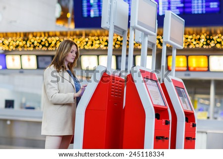 Young woman at international airport, checking in on electronic terminal waiting for her flight. Female passenger at terminal, indoors. - stock photo