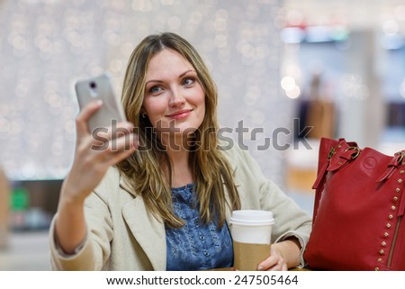 Young woman  at international airport, making selfie with mobile phone and waiting for her flight. Female passenger at departure terminal, indoors. - stock photo