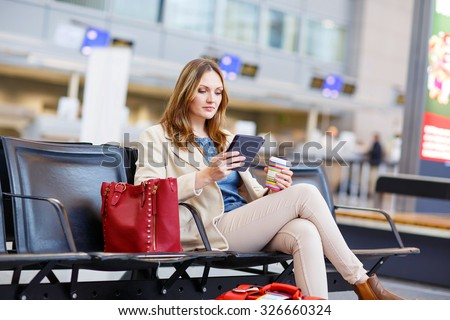 Young woman at international airport, reading her ebook and drinking coffee while waiting for her flight on business trip. Female passenger at terminal, indoors. - stock photo