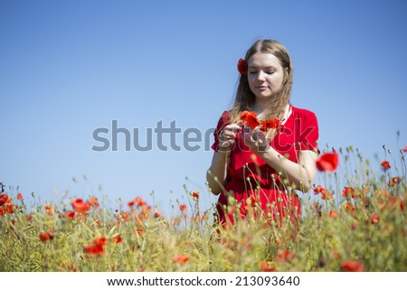 Young woman at red dress collect poppy blossoms - stock photo
