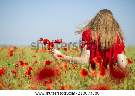Young woman at red dress with poppies bouquet - stock photo