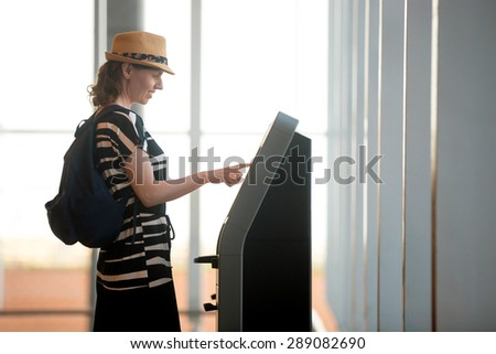 Young woman at self service transfer area doing self-check-in or buying plane tickets at automated machine with touchscreen interactive display in modern airport terminal building - stock photo