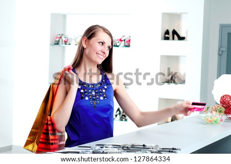 Young woman at shopping mall checkout counter paying through credit card - stock photo