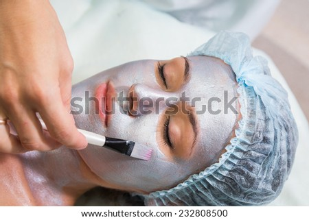 Young woman at spa procedures applying mask. Therapist applying a face mask to the face of a beautiful young  woman using a cosmetic brush.Cosmetology,facial, beauty - The concept of facial skin care. - stock photo