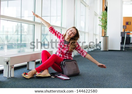 young woman at the airport playing like she can fly - stock photo