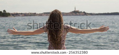 Young woman at the beach jetty with arms open enjoying freedom - stock photo