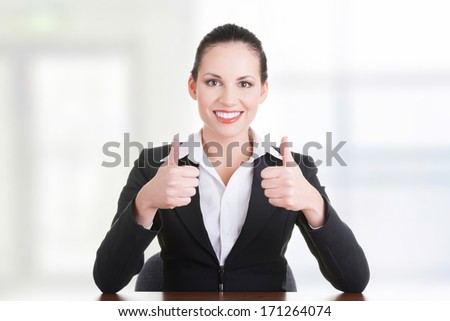 Young woman at the desk gesturing OK - stock photo