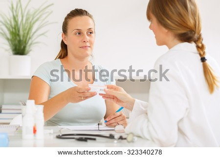 Young woman at the doctors office getting medication and health advice - stock photo