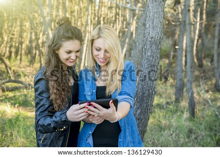 young woman at the park using a digital tablet - stock photo