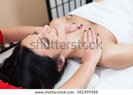 Young woman at the spa receiving back massage and enjoying with her eyes closed - stock photo