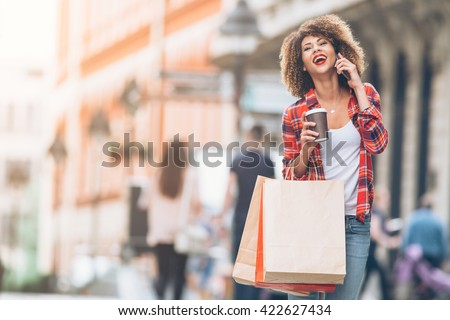 Young woman at the street with shopping bags talking on mobile phone  - stock photo